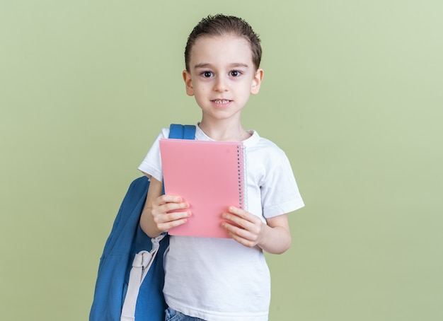 Довольный маленький мальчик в рюкзаке смотрит в камеру, показывая блокнот, изолированный на оливково-зеленой стене с копией пространства