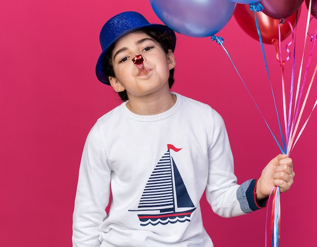 Pleased little boy wearing blue party hat holding balloons blowing party whistle