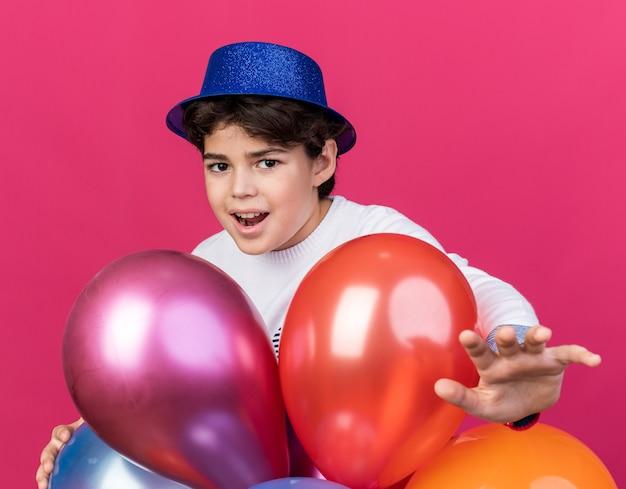 Felice ragazzino che indossa un cappello da festa blu in piedi dietro i palloncini che tengono la mano alla telecamera