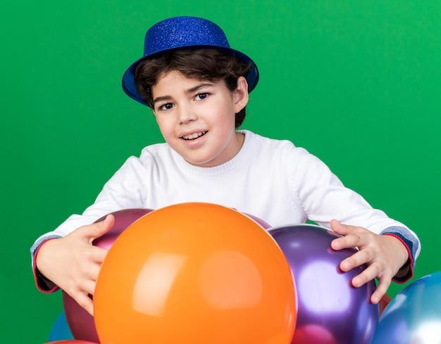 緑の壁に隔離された風船の後ろに立っている青いパーティーハットをかぶって喜んで少年