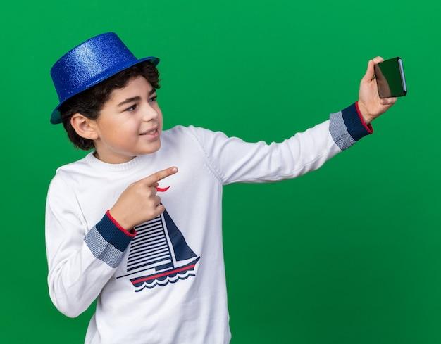 青いパーティーハットをかぶって喜んでいる小さな男の子は、緑の壁に隔離された正面で自分撮りポイントを取る