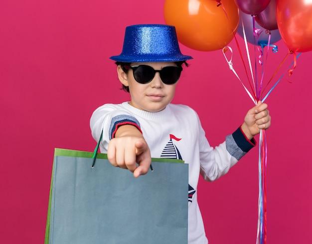 ピンクの壁に隔離されたジェスチャーを示す風船とギフトバッグを保持しているメガネと青いパーティーハットを身に着けている小さな男の子を喜ばせます