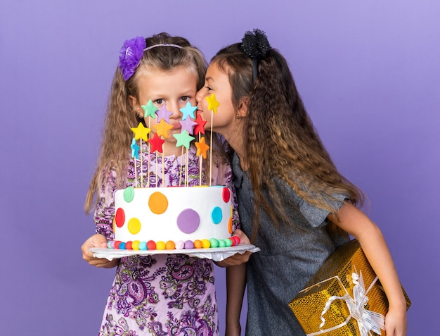 Compiaciuta piccola ragazza caucasica con confezione regalo e baciare triste bimba bionda con torta di compleanno isolata sulla parete viola con spazio copia