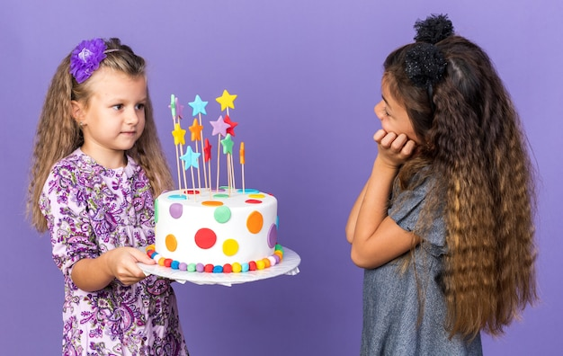 Pleased little caucasian girl holding hands together and looking at blonde little girl holding birthday cake isolated on purple wall with copy space