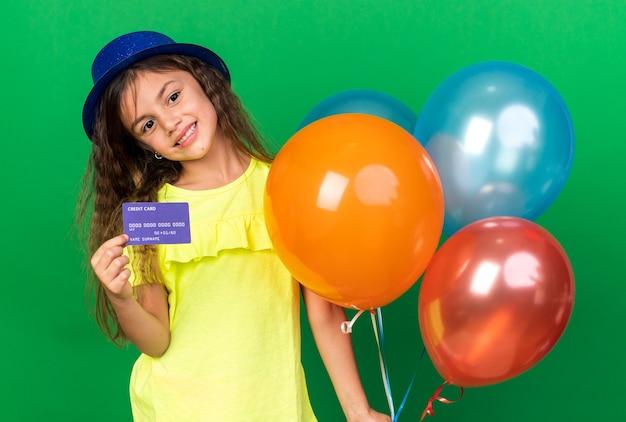Lieta piccola ragazza caucasica con cappello blu del partito che tiene palloncini di elio e carta di credito isolata sulla parete verde con lo spazio della copia