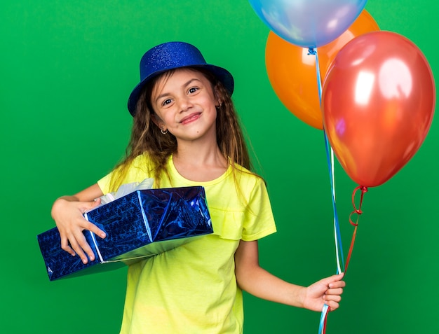 Pleased little caucasian girl with blue party hat holding helium balloons and gift box isolated on green wall with copy space