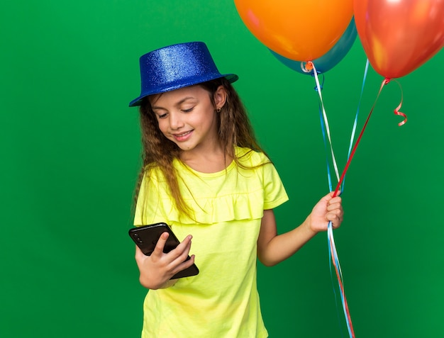 Pleased little caucasian girl with blue party hat holding helium balloons and looking at phone isolated on green wall with copy space