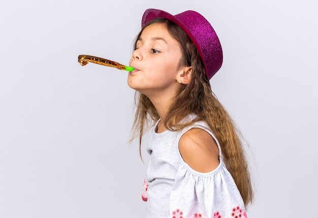 Pleased little caucasian girl with purple party hat blowing party whistle looking at side isolated on white wall with copy space