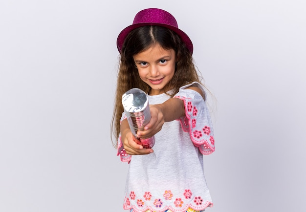 Pleased little caucasian girl with purple party hat holding confetti cannon isolated on white wall with copy space