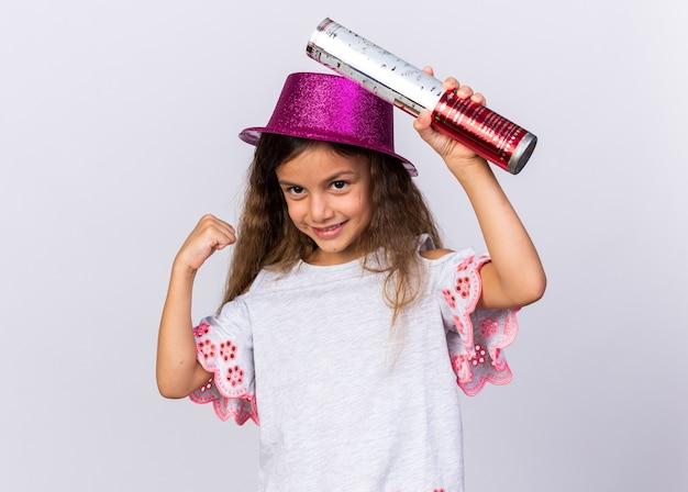 Contenta piccola ragazza caucasica con cappello da festa viola che tiene cannone coriandoli e bicipiti tesi isolati sul muro bianco con spazio copia