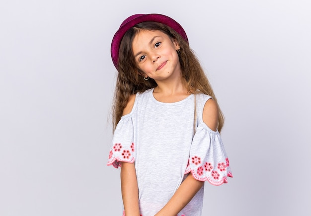 Довольная маленькая кавказская девушка в фиолетовой шляпе, изолированной на белой стене с копией пространства