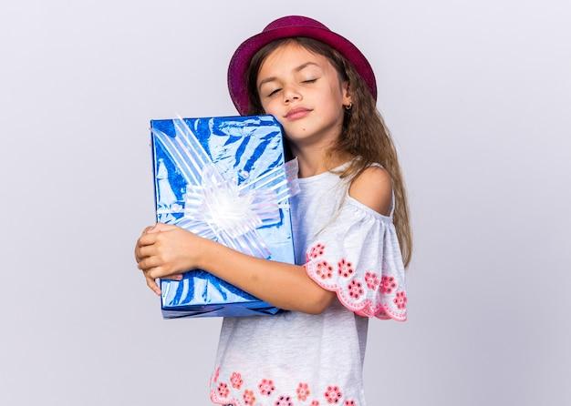Довольная маленькая кавказская девушка с фиолетовой шляпой, стоящая с закрытыми глазами, держит подарочную коробку, изолированную на белой стене с копией пространства