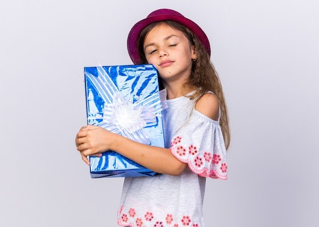 Pleased little caucasian girl with purple party hat standing with closed eyes holding gift box isolated on white wall with copy space