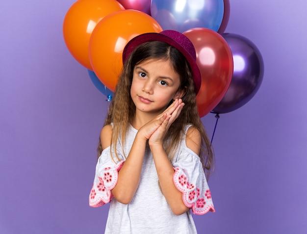 Lieta piccola ragazza caucasica con il cappello viola del partito che tengono le mani insieme in piedi davanti a palloncini di elio isolati sulla parete viola con lo spazio della copia