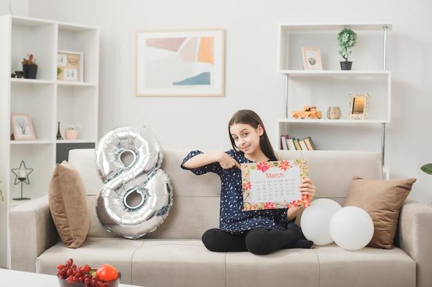 Довольная маленькая девочка в счастливый женский день держит и указывает на календарь, сидя на диване в гостиной