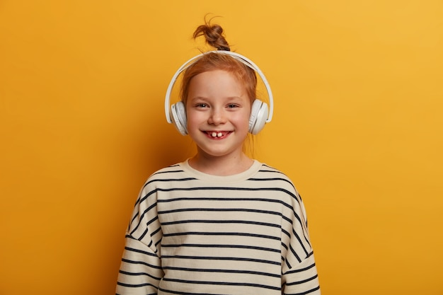 Pleased little girl with hair bun wears striped jumper, giggles positively, listens audio track in headset, has upbeat mood, smiles toothily, enjoys favorite song, isolated over yellow wall
