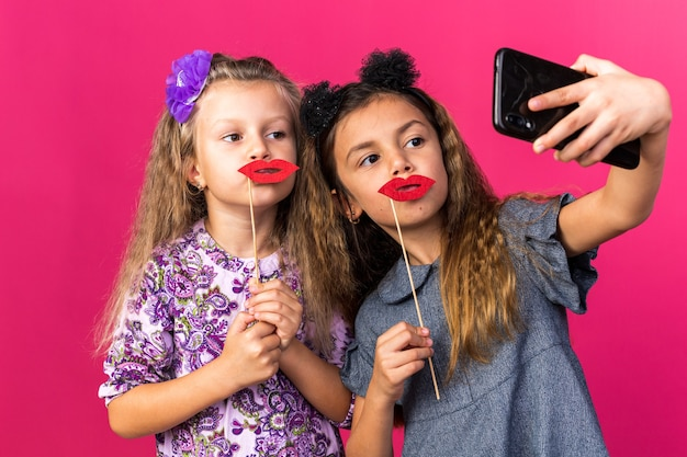 Compiaciute bambine graziose che tengono labbra finte su bastoncini che si fanno selfie isolati su una parete rosa con spazio per le copie