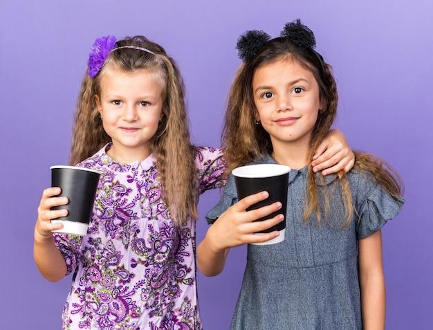 Довольные маленькие красивые девушки держат бумажные стаканчики на фиолетовой стене с копией пространства