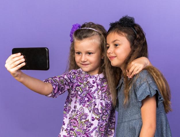 Довольные маленькие красивые девушки смотрят на телефон и делают селфи на фиолетовой стене с копией пространства