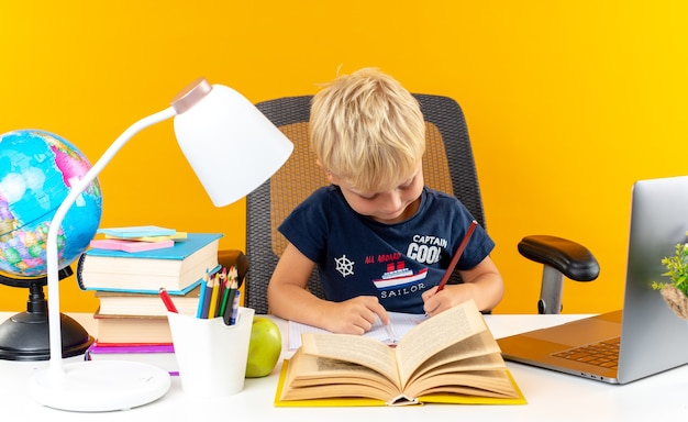 공책에 뭔가를 쓰는 학교 도구와 함께 테이블에 앉아 기쁘게 작은 학교 소년