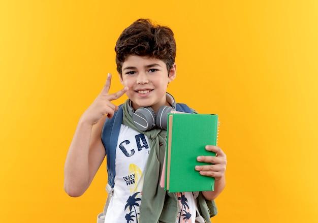 다시 가방과 책을 들고 헤드폰을 착용하고 노란색 배경에 고립 된 평화 제스처를 보여주는 기쁘게 작은 학교 소년