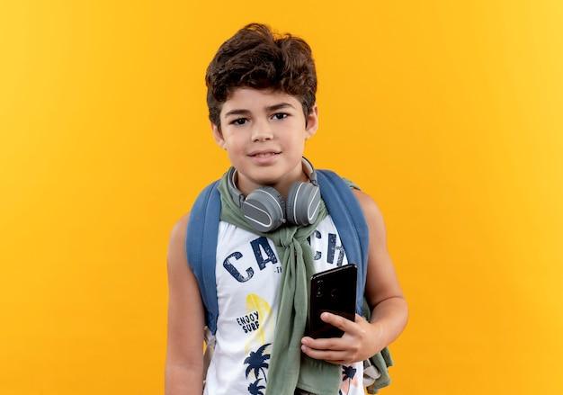 다시 가방과 노란색 배경에 고립 된 전화를 들고 헤드폰을 입고 기쁘게 작은 학교 소년