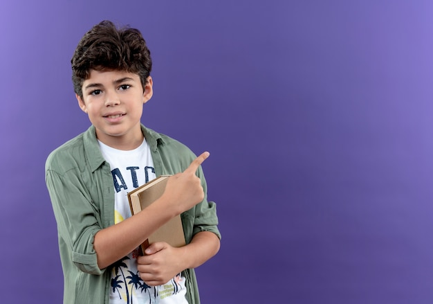 Pleased little schoolboy holding book and points at side isolated on purple wall with copy space