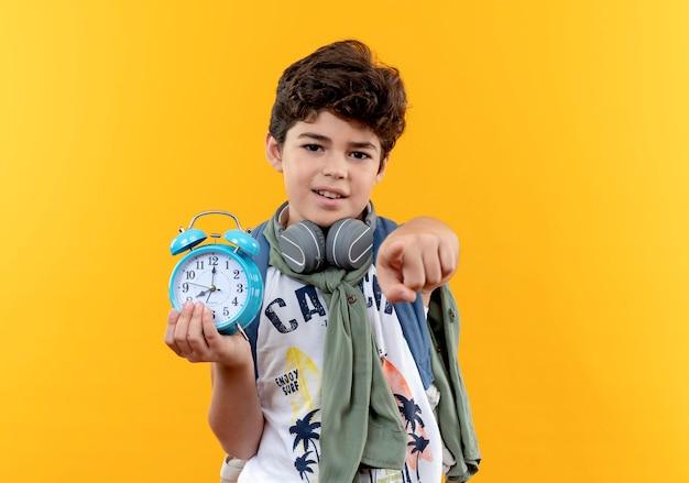 黄色の背景に分離されたカメラで目覚まし時計とポイントを保持しているバックバッグとヘッドフォンを身に着けている小さな男子生徒を喜ばせます