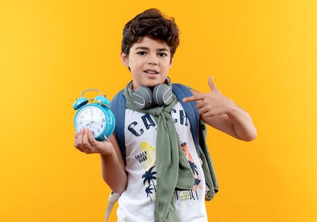 黄色の背景で隔離の目覚まし時計を保持し、ポイントバックバッグとヘッドフォンを身に着けている小さな男子生徒を喜ばせます