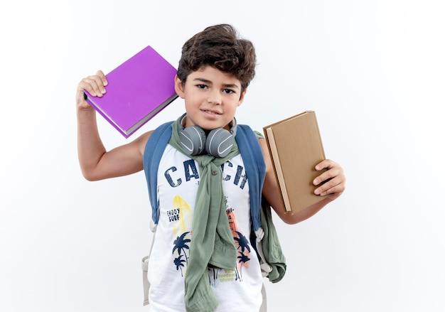 白い背景で隔離の本を保持しているバックバッグとヘッドフォンを身に着けている小さな男子生徒を喜ばせる