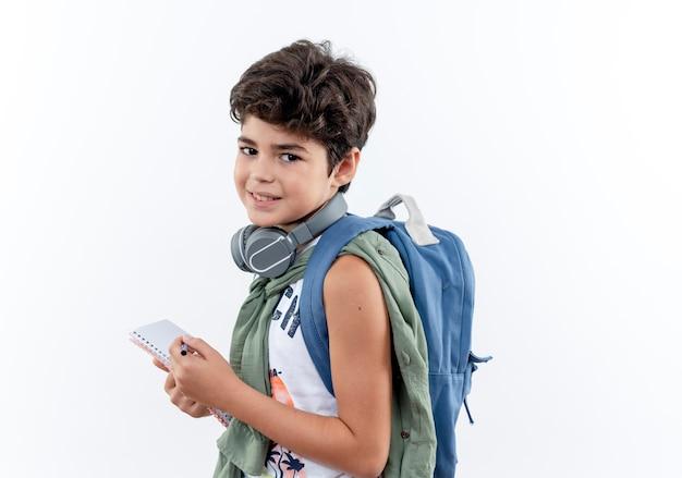 白い背景で隔離のノートとペンを保持しているバックバッグとヘッドフォンを身に着けている小さな男子生徒を喜ばせる