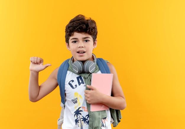 黄色の背景で隔離のノートを保持しているバックバッグとヘッドフォンを身に着けている小さな男子生徒を喜ばせる