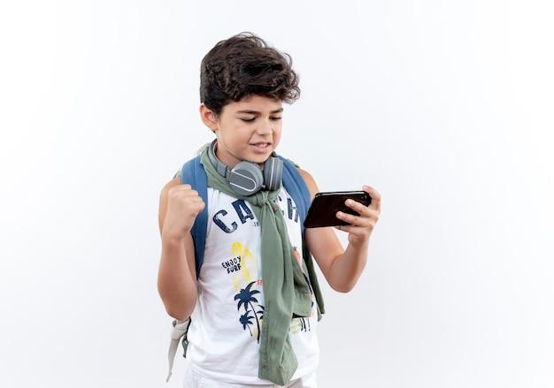 다시 가방과 전화에서 재생 헤드폰을 착용 하 고 흰색 배경에 고립 예 제스처를 보여주는 기쁘게 작은 모범생