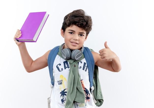 白い背景で隔離の彼の親指を上げてバックバッグとヘッドフォンを身に着けている小さな男子生徒を喜ばせる