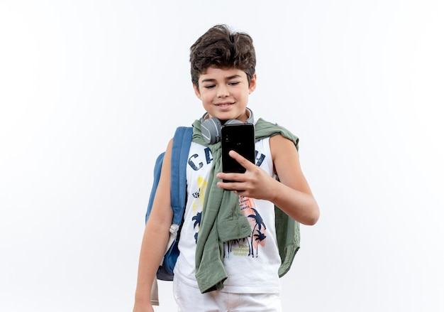 Pleased little schoolboy wearing back bag and headphones holding and looking at phone isolated on white background