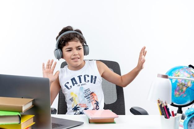 Felice piccolo scolaro che indossa le cuffie seduto alla scrivania con strumenti di scuola ascolta musica isolata su sfondo bianco