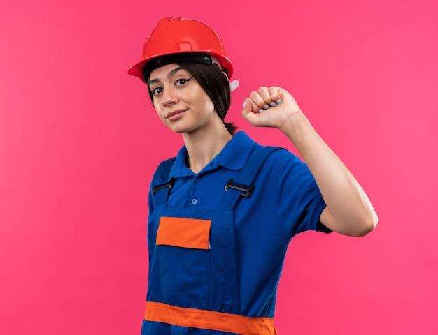 強いジェスチャーをしている制服を着た若いビルダーの女性のカメラを見て喜んで