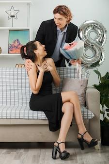 リビングルームで女の子とソファで後ろに立っている花束を持っている幸せな女性の日の男でお互いの若いカップルを見て喜んで