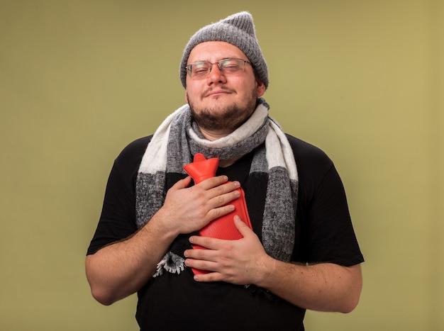 冬の帽子とオリーブグリーンの壁に隔離された湯たんぽを保持しているスカーフを身に着けている正面の中年の病気の男性を見て喜んで