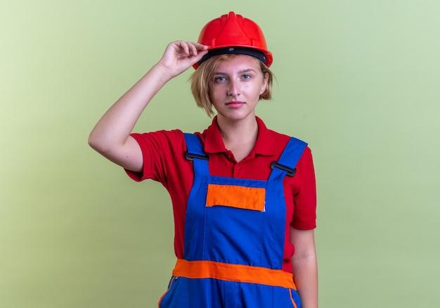 올리브 녹색 벽에 격리된 제복을 입은 젊은 건축업자 여성을 바라보는 것을 기쁘게 생각합니다.