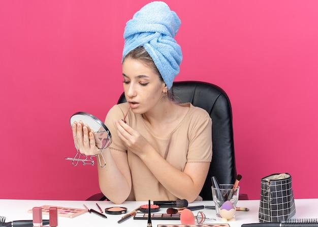 Довольно глядя в зеркало, молодая красивая девушка сидит за столом с инструментами для макияжа, завернув волосы в полотенце, применяя блеск для губ, изолированные на розовой стене