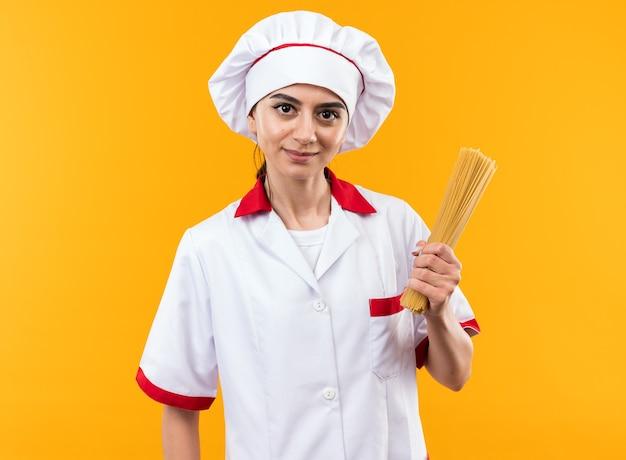 Довольно глядя на сторону молодой красивой девушки в униформе шеф-повара, держащей спагетти