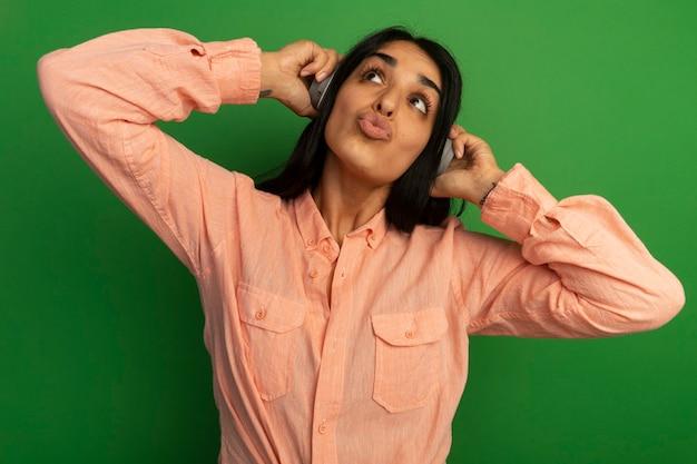 Довольно глядя на сторону молодой красивой девушки в розовой футболке с наушниками, изолированной на зеленой стене