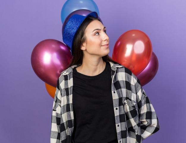 青い壁に分離された前の風船に立っているパーティーハットを身に着けている若い美しい女性の横を見て喜んで