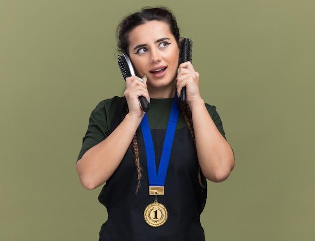 올리브 녹색 벽에 고립 된 귀 주위에 빗을 들고 유니폼과 메달 측면 젊은 여성 이발사를보고 기쁘게 생각합니다.