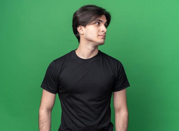 복사 공간 녹색 벽에 고립 된 검은 티셔츠를 입고 측면 젊은 잘 생긴 남자를보고 기쁘게 생각