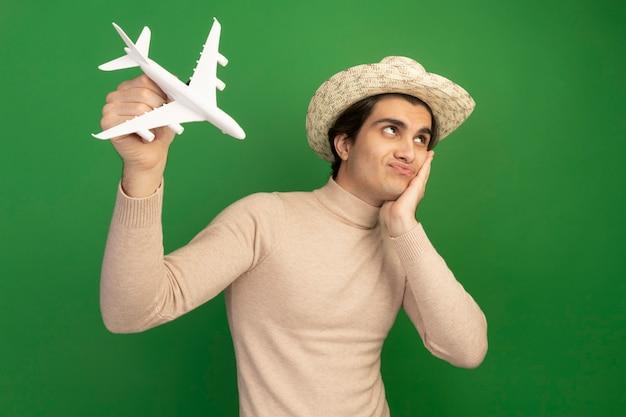 帽子をかぶった若いハンサムな男の側を見て、緑の壁に隔離された頬に手を置いておもちゃの飛行機を上げる