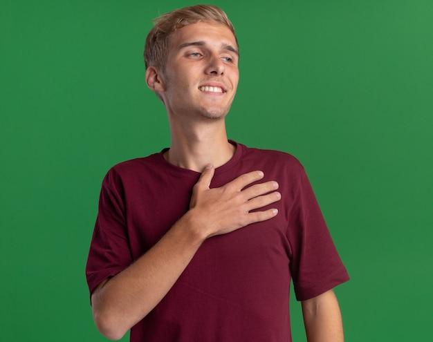 緑の壁で隔離の心に手を置いて赤いシャツを着ている若いハンサムな男を見て喜んで