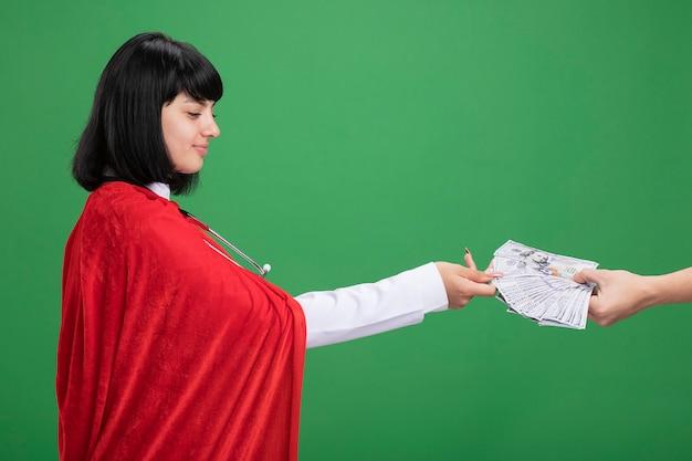 医療ローブと聴診器を身に着けている側の若いスーパーヒーローの女の子を見て喜んで、緑に隔離された彼女にお金を与えている誰かをマント