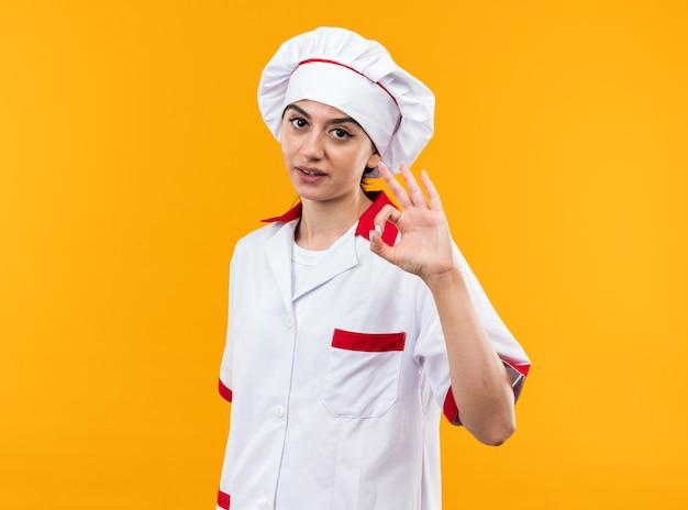 Piacere guardando la telecamera giovane bella ragazza in uniforme da chef che mostra un gesto ok